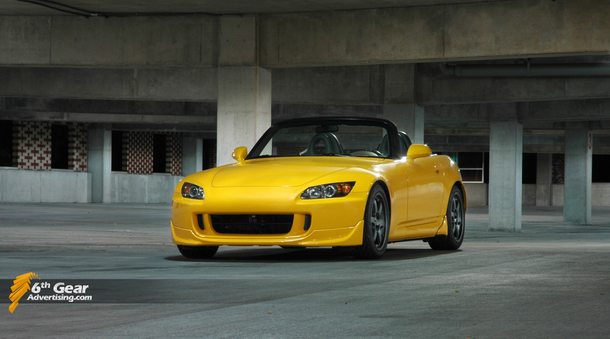 Yellow Honda S2000 AP1 shot in a parking garage.